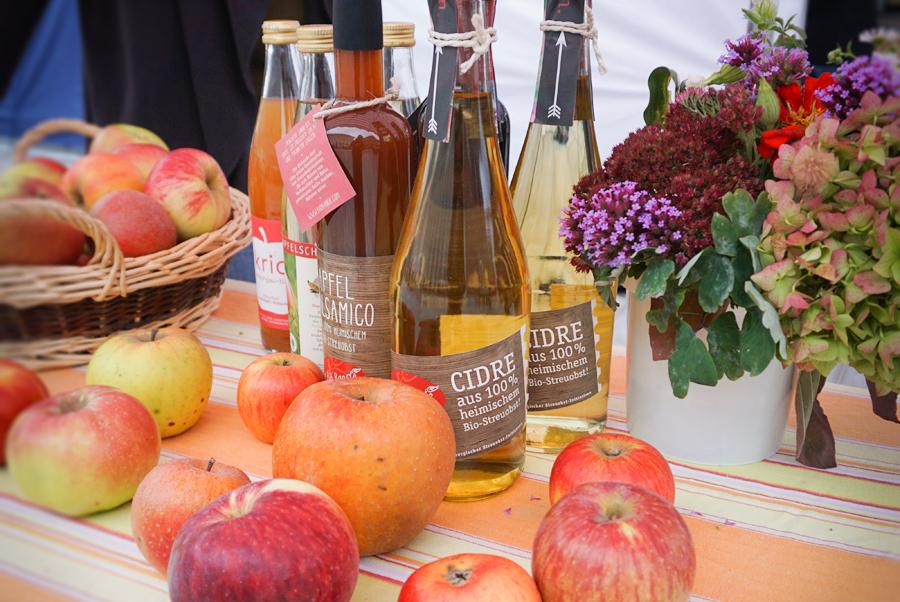 Cidre, Balsamico und Äpfel mit einem Blumenstrauß auf einem Tisch