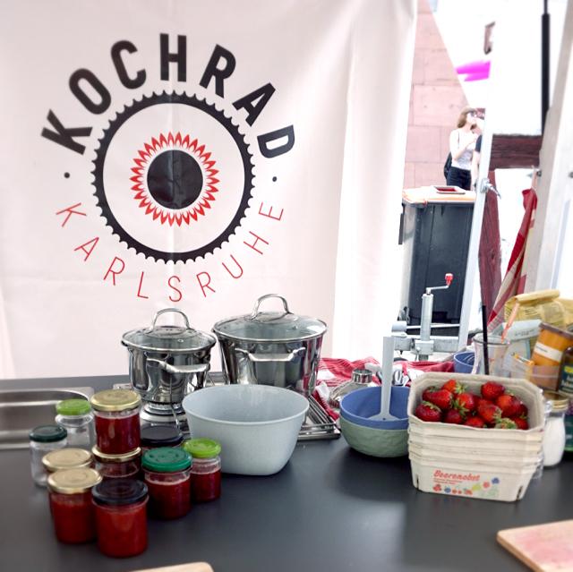 Kochrad mit Erbeerschale und Marmeladegläsern